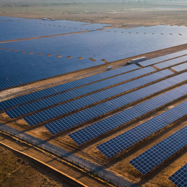 Solar power station - a view from above. Long rows of solar panels - large blue rectangles on a background of yellow sandy soil. Perfectly even rows - a beautiful futuristic landscape. Photo from a copter at sunset.